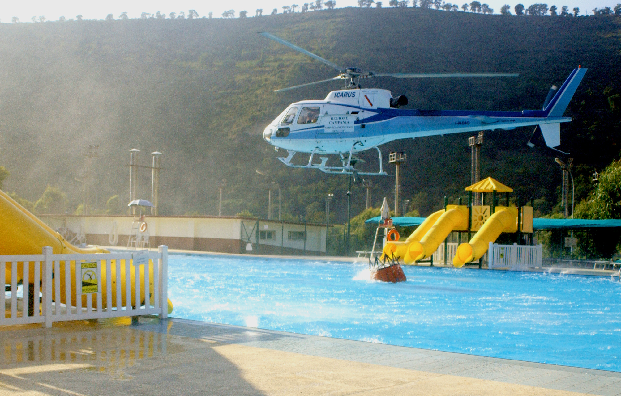 Firefighting helicoper fills water bag from public swimming ...
