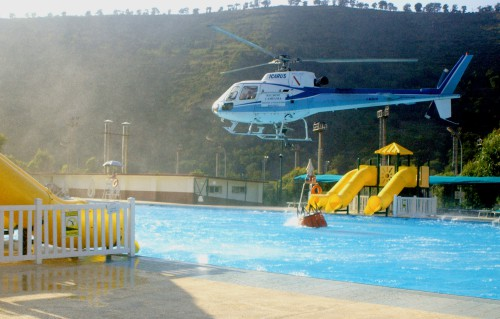 An Italian firefighting helicopter loads up its 125-gallon bag with water from the Carney Park public swimming pool aboard Naval Support Activity (NSA), Naples, while assisting local authorities with fighting local wild fires. The Italian firefighters contacted the NSA Fire Department requesting use of the pool, which helped reduce turn-around time from four to five minutes to less than 60 seconds. U.S. Navy photo by Journalist 1st Class Stephen Woolverton (RELEASED), Sept 1 2004.