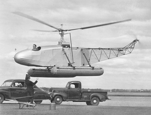 The Sikorsky VS-300 hovering under the watchful eyes of its inventor, Igor Sikorsky (standing). The VS-300 was the first successful single lifting rotor helicopter in the US and the first successful helicopter to use a single vertical-plane tail rotor configuration for antitorque. With floats attached (as in this image), it took off and landed from the water in 1941, thus also becoming the first practical amphibious helicopter. From Vertiflite, May/June 1974 (page 5).