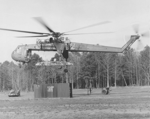 "US Army CH-54 Tarhe prepares to pick up a 20-ft ""Mil-Van"" container as part of a demonstration to conduct pickup, transport, and release all without ground crew assistance. The demonstration was conducted Dec. 19, 1973 at Ft. Eustis, VA, with help from the 355th Aviation Company, under the direction of engineers from the Army's Air Mobility R&D Laboratory (AMRDL), Eustis Directorate. From Vertiflite, March/April 1974 (page 34)."