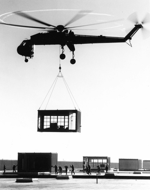 An Erickson Air-crane Skycrane lowers one of 39 direct-fired make-up air heaters into position atop Caterpillar Tractor Company's new basic engine plant under construction in Mossville, Illinois. Maker of the heaters, Dravo Corp. in Pittsburgh, moved them part way by barge. Each unit measured 32 by 22 ft by 12 ft high. From Vertiflite, March/April 1974 (page 30).