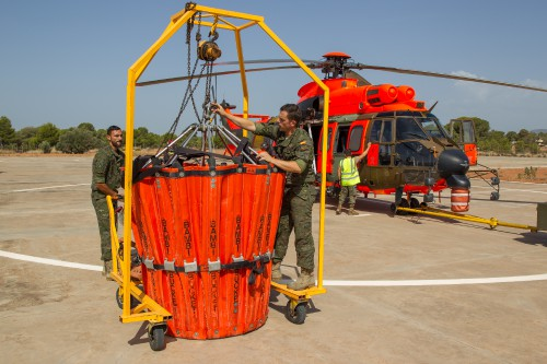 A Bambi Bucket BBT 6578 HD being fitted to an AS532AL Cougar operated by the 2nd Emergency Battalion (Batallón de Helicópteros de Emergencia II) of the Spanish Army Airmobile Force (Fuerzas Aeromóviles del Ejército de Tierra, FAMET). Bambi Bucket BBT 6578 HD is the largest version available for the battalion. It can carry up to 2,850 liters (750 gal) of water. At the base, the bucket is stored in this metal frame to enable the crews to deploy quickly. The Bambi Bucket normally can be flown to a maximum of 80 kt (148 km/h) indicated airspeed while conducting external cargo hook operations. The BHELEME II pilots typically fly at 50–70 kt (90–130 km/h). From Vertiflite, March/April 2017 (page 45).