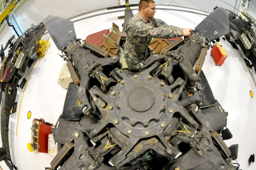 U.S. Army Spc. Todd Gann, 1-135th Attack/Reconnaissance Battalion aircraft maintainer, inspects the main rotor head of an AH-64 Apache at Whiteman Air Force Base, Mo., Jan. 9, 2014. Soldiers perform this inspection annually to ensure there are no signs of corrosion developing, which could cause malfunctions. (U.S. Air Force photo by Airman 1st Class Keenan Berry/Released) Source: http://www.whiteman.af.mil/News/Features/Display/Article/836355/teamwork-and-dedication-from-the-ground-to-the-sky/