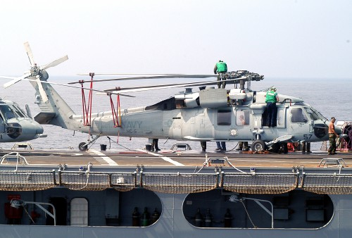 Airmen from USNS Niagara Falls (T-AFS-3) are seen conducting maintenance on top of an SH-60S Seahawk during a recent underway replenishment with USS Blue Ridge (LCC 19). U.S. Navy photo by Photographer's Mate Airman Apprentice Tucker Yates. (RELEASED) 19 August 2003.