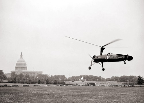 Shuttle mail delivery demonstrated, Washington, D.C., May 19, 1938. The feasibility of a shuttle airmail service was demonstrated as part of National Airmail Week when an autogyro, piloted by John Miller, landed on the city post office grounds with a cargo of mail from the branch post office at Washington airport. The U.S. Capitol can be seen in the background. The aircraft, NC14742, was actually a prototype for the KD-1. Source: https://commons.wikimedia.org/wiki/File:Autogyro_Shuttle_mail_delivery_demonstrated_25025v.jpg