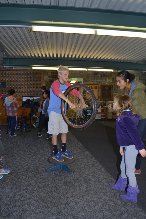 Using a bicycle wheel and turntable, a volunteer taught their audience about gyroscopic stability and conservation of momentum.