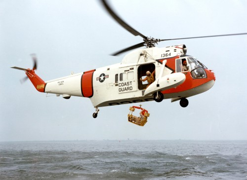 A U.S. Coast Guard Sikorsky HH-52A Seaguard helicopter (s/n 1364) with a rescue basket. Although the rescue basket and hoist had been developed and put into use by the time the HH-52 entered service the Coast Guard did not have the trained personnel to actually jump in the water to assist injured or incapacitated survivors. The only exception to this was if the co-pilot volunteered to jump in (and the aircraft commander approved)--the aircrewman had to stay on board the aircraft to operate the hoist; consequently survivors were required to get into the lowered basket themselves. Some units experimented with what became known as rescue swimmers but it was not until the 1980s that the service formally instituted a rescue swimmer program.