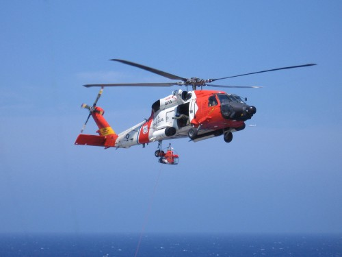 "This photo, taken by Carl Russell, shows a US Coast Guard HH-60J Jayhawk out of CGAS Clearwater performing an at-sea rescue of a cruise ship passenger who needed to be evacuated due to a medical emergency. Off the nose, an HC-130 is circling in the distant background.  Third-place awardee in the 2018 AHS Photo Contest in the category of ""Vertical Flight in Action!"""