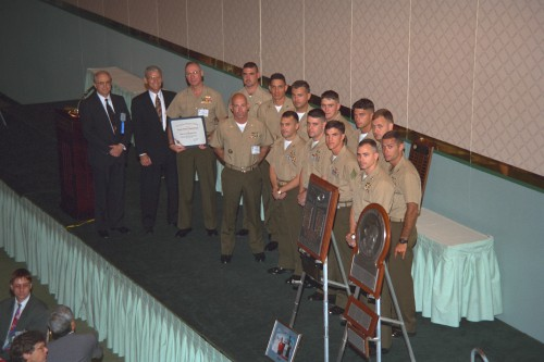 Captain William J. Kossler Award at annual Forum 52, 1996 was awarded to Crew Members of the Marine corps aviation team which in June 1995 performed the successful rescue of USAF Captain Scott O'Grady in Bosnia.  This extraordinary effort illustrated the high degree of technology, teamwork and training needed to ensure the mission's success. Forum 52 Awards Banquet at the Sheraton Washington Hotel, Washington, D.C., June 5, 1996. VFS photo. CC BY-SA 4.0.