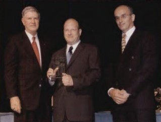 Supplier Excellence Award at Forum 58, 2002, won by Helicopter Support, Inc.(HSI), for notable contributions in the vertical flight industry. Society Chairman John Murphey congratulates David Adler, company president and John Chimini, executive vice president, HSI.  Forum 58, June 11-13, 2002, Montréal, Québec Canada