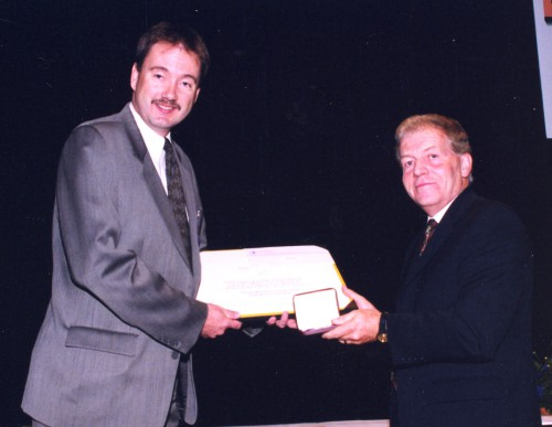 Grover E. Bell Award 2003 presented to Flight Research Laboratory, NRC Canada, at annual Forum 59 Awards, for conducting world class vertical takeoff and landing research since the 1950s. The Chairman of Society Gilles Ouimet congratulates Steward Baillie, the representative of the National Research Council, Canada's Flight Research Laboratory.  Forum 59, May 6-8, 2003, Phoenix, Arizona USA
