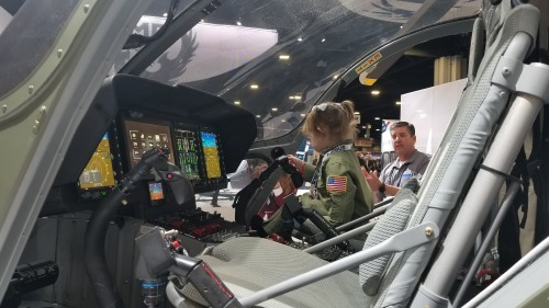 A future aviator checks out the glass cockpit of the MD Helicopters MD 969 Combat Explorer — a derivative of its MD 902 Explorer — unveiled at Heli-Expo 2019. (VFS photo taken on March 7, 2019, Atlanta, Georgia. CC-BY-SA 4.0)