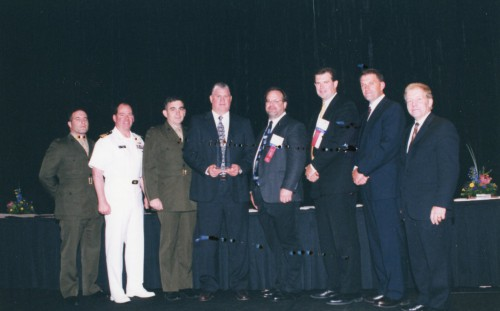 Supplier Excellence Award at Forum 59 Awards, 2003 presented to Rolls Royce AE1107C Liberty Propulsion System Team, Rolls Royce, for notable contributions within the vertical flight industry. Gilles Ouimet congratulates team representatives - James Haney, Stuart Mullan, James Jackson and Steve Fromknecht, Rools Royce; Col. Paul Crossetiere, USMC; Commander Steve Malloy, USN; Major Ullmark, USMC, V-22 Program Office on stage.  Forum 59, May 6-8, 2003, Phoenix, Arizona USA