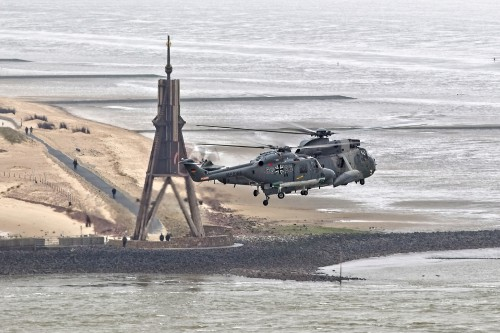 "A Leonardo/Westland Sea King (background) and Sea Lynx (foreground) fly past the historic ""Kugelbake"" beacon, a landmark near Nordholz Naval Air Station. These photos of Marinefliegergeschwader (MFG) 5 in action accompany the article ""German Navy Helicopter Fleet Still Going Strong,"" by Anno Gravemaker, in the Vertiflite Sep/Oct issue. Photo taken June 19, 2019 by Anno Gravemaker CC BY-NC-SA 4.0."