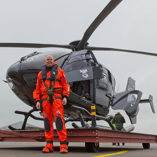 """Vertiflite author Anno Gravemaker in front of an Airbus EC 135 used for flight training of the Marineflieger crews. The aircraft is wearing the MFG 5 badge but is on lease from a private company. These photos of Marinefliegergeschwader (MFG) 5 in action accompany the article """"German Navy Helicopter Fleet Still Going Strong,"""" by Anno Gravemaker, in the Vertiflite Sep/Oct issue. Photo taken June 19, 2019 by Anno Gravemaker CC BY-NC-SA 4.0."""