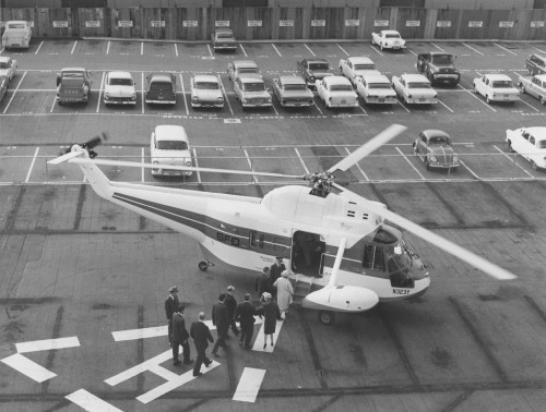 HELICOPTER PASSENGERS BOARD a Sikorsky S-62 parked on the downtown San Francisco heliport of the San Francisco & Oakland Helicopter Airlines. The heliport adjoins the World Trade Center in the Ferry Building, which is in the heart of the financial district.