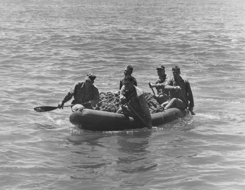 MISSION BOUND.  Marine reconnaissance scouts head for shore after Sikorsky S-55 helicopter drop. Clockwise, starting at the left, are Cpl. Harold D. Dickinson of Framingham, Mass., S/Sgt William V. Schmitz of Newton, N.J., Lt. Col. Ephraim Kirby-Smith of Sewanee, Tenn., commanding officer of the Second Reconnaissance Battalion, Second Marine Division; Sgt. Lewis L. Bryant of Allentown, Pa., and Irving B. Tchakirides of Waterbury, Conn.  1955