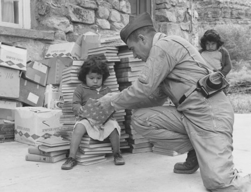 """Lt. Col. William R. Duncan, commanding officer of HMH-462, helps Shirley Watahomigie, 2, turn pages of books Marines brought Havasupais. More than 5,000 volumes will help form library for new school. Shirley's sister, Belinda, 5, is shown at right. Title of volume at top of stack may seem ironic to Indians; it's """"New Ways in the New World.""""  Sikorsky Aircraft photo, February 2, 1964."""