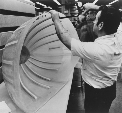 CHECKING SPECS OF SPONSON SECTION  Production inspector checks dimensions of daillyl phthalate-molded sponson (float) section of Sikorsky helicopter. Daillyl phthalate prepregs lend themselves to the hand lay-up process because of their good tack and drape.   Sikorsky Aircraft photo