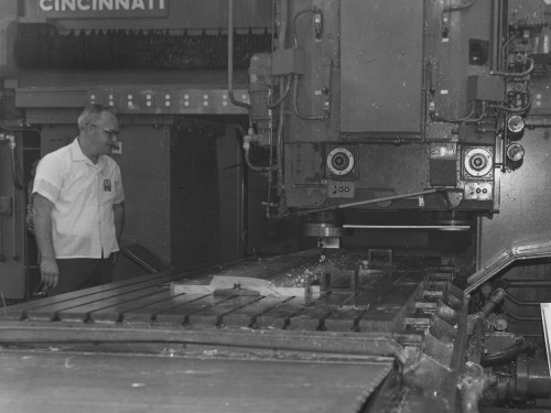 FOR IMMEDIATE RELEASE  Stratford, Connecticut -- Numerically-controlled bridge-milling machine at Sikorsky Aircraft rough cuts seven-foot length of aluminum spar, part of master aluminum mandrel for advanced rotor blade spar. New method developed by manufacturing engineering department saves time and money.  December 10, 1970.  Sikorsky Aircraft photo
