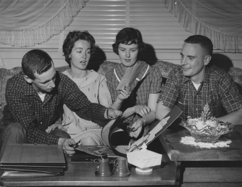 FOR RELEASE SUNDAY, JULY 23, 1961.  PROUD WIVES: Mrs. George F. Cox, left, and Mrs. Wayne E. Koons, look over scrap-book with Lieutenants Cox and Koons in the Koons' home at the Marine Corps Air Facility, New River, N.C. Helicopter pilots picked up Commander Shepard following epic space flight of May 5, 1961.  Sikorsky Aircraft photo. Page 6, Figure 7, from Vertiflite (AHS Newsletter) Aug 1961.