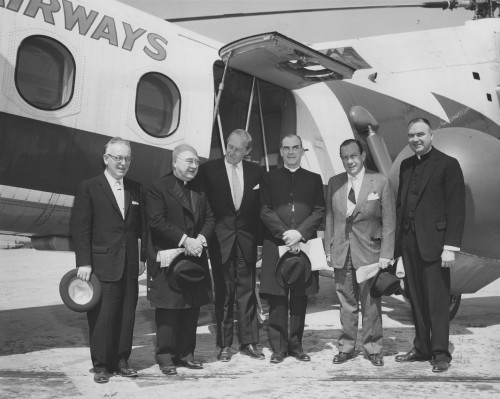 """New York Airways  DIGNITARIES FLY HELICOPTER - - A GROUP OF RELIGIOUS AND CIVIC DIGNITARIES FLEW TO THE DEDICATION OF ONE OF THE COUNTRY'S NEWEST SCENIC WONDERS IN A NEW YORK AIRWAYS' HELICOPTER EARLY IN MAY. STERLING FOREST GARDENS, A 125 ACRE CULTURAL PHENOMENA, ARRANGED FOR THE GROUP TO FLY FROM MANHATTAN'S MID-MANHATTAN HELIPORT AT WEST 30th STREET AND THE HUDSON RIVER TO TUXEDO, NEW YORK, IN A 25 MINUTE FLIGHT. IT PROVIDED A """"CLOSE-UP"""" AIRBORNE LOOK OF THE CITY FOR THE PASSENGERS.   Left to right: Rabbi Joel S. Geffen, Director of the Department of Community Education of the Jewish Theological Seminary of America; His Eminence Francis Cardinal Spellman, Catholic Bishop of New York; Robert w. Dowling, President of Sterling Forest Gardens and City Investing Company; Bishop Charles F. Boynton, Senior Suffragan Bishop of the Episcopal Church in New York; Mayor Robert Wagner of New York; and Right Reverend Monsignor Edwin B. Broderick, secretary to Cardinal Spellman.  New York Airways photo"""