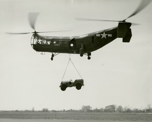 Left side view of Piasecki XHRP-1 Rescuer (Flying Banana) in flight, lifting a 1-ton Navy Jeep above a field, circa late 1940s. Photo used with permission of the Smithsonian Institution, National Air and Space Museum.